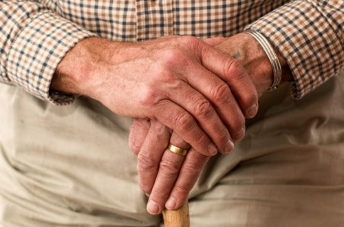 old man's hand on walking cane